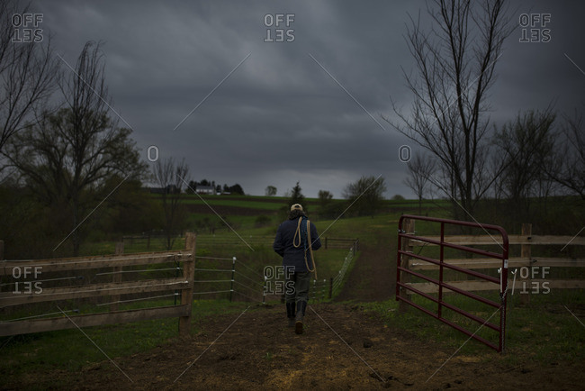Man carrying ropes into a pasture on a stormy day