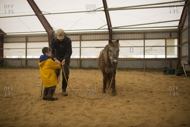 Woman handing a pony's lead rope to a little boy