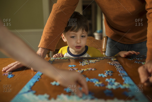 Boy watching as two adults put together a puzzle