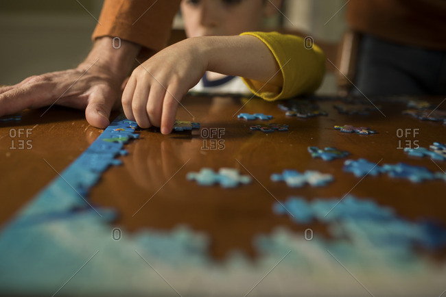 Boy helping father put together a puzzle