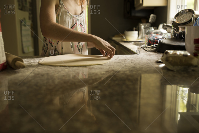 Girl with freshly rolled dough on a stone countertop