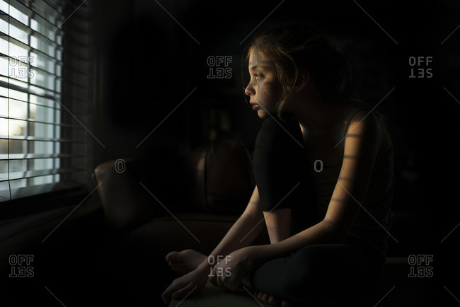 Girl in a darkened room looking out window blinds