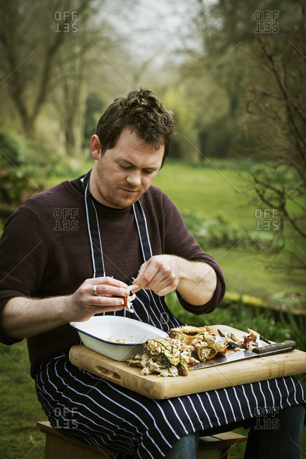 Chef sitting outdoors with a chopping board on his lap, preparing a crab