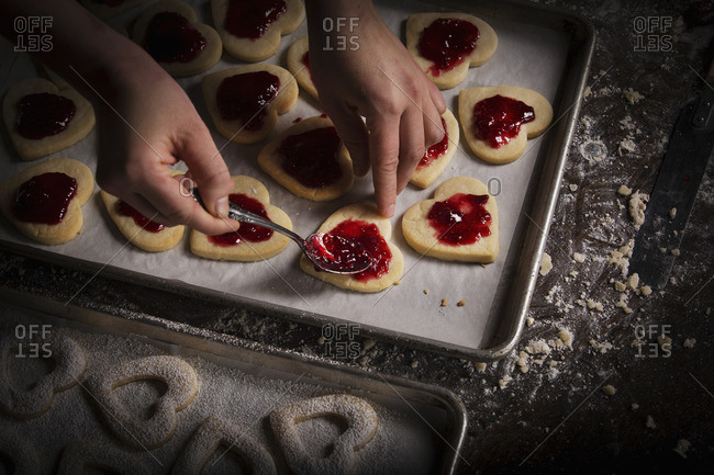 Woman spreading raspberry jam on heart shaped cookies