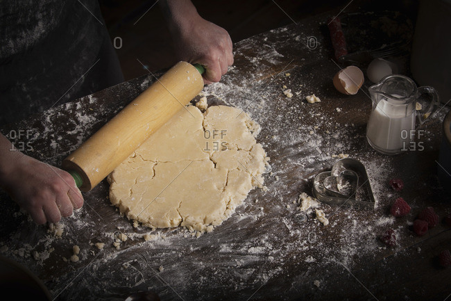 Baker rolling out dough with a rolling pin