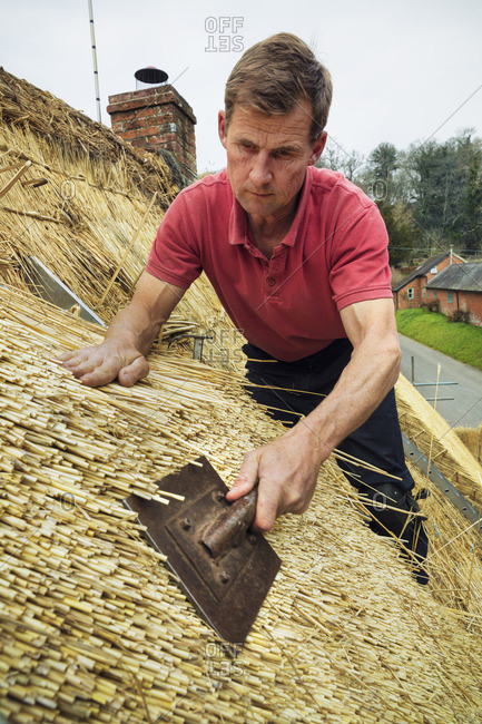 Man standing on a ladder, dressing the thatch roof using a leggett