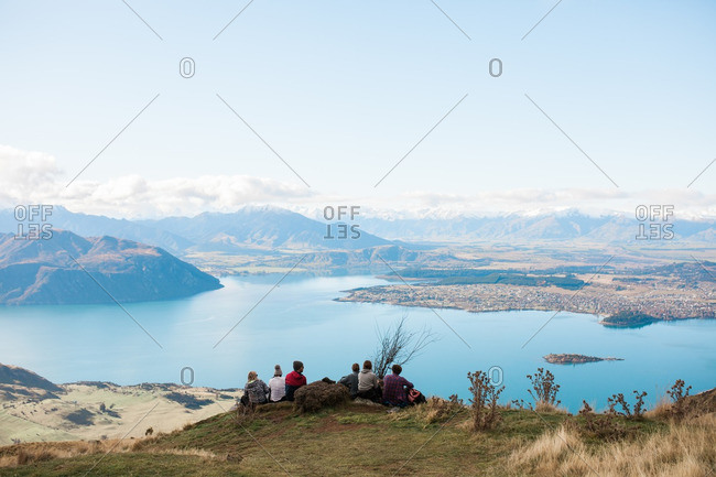 Group of people sitting on a rocky ridge overlooking a mountain lake