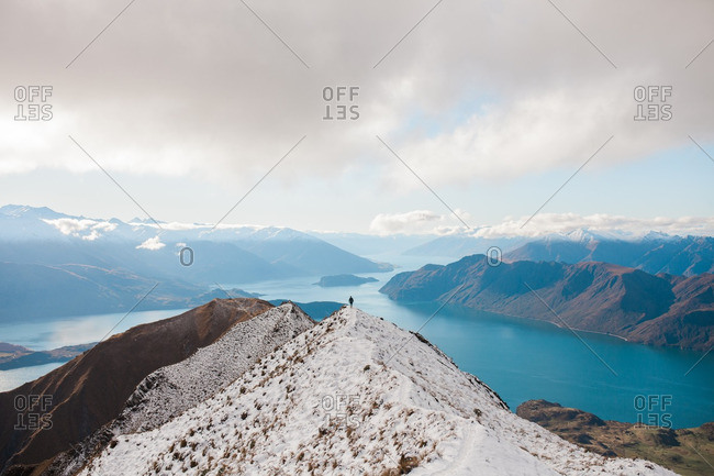 Person standing on top of a snow covered mountain ridge