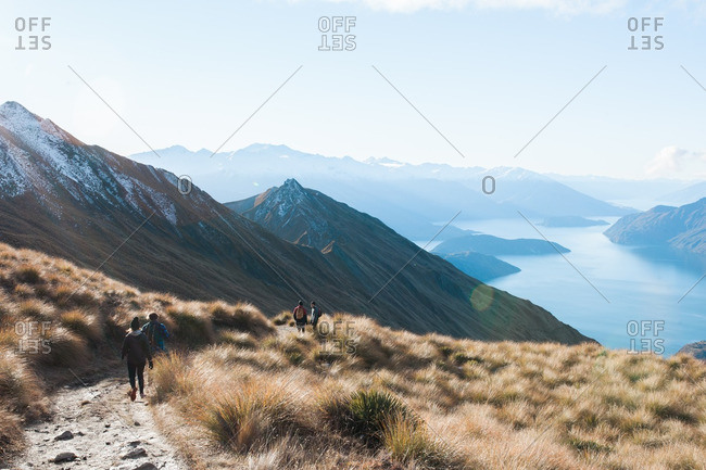 Group of people hiking down a mountain trail