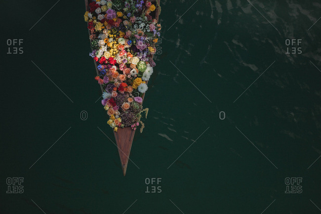 Overhead view of a small wood boat filled with colorful flowers