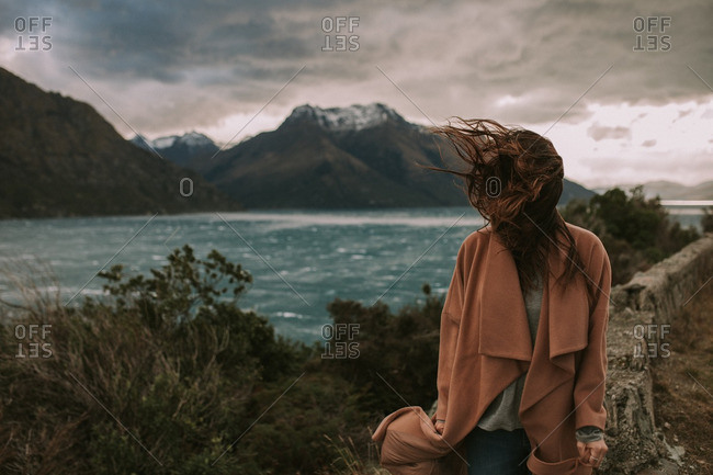 Woman standing along a windswept shoreline surrounded by rugged mountains