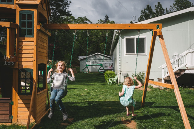 Two girls swinging together on a swing set