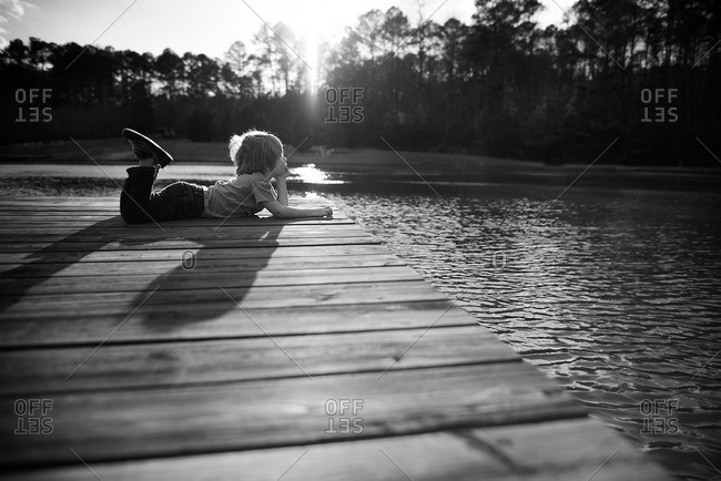 Boy looking out from dock at sunset