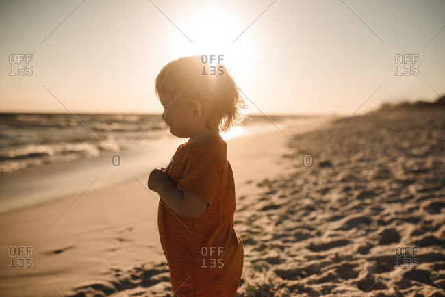 Baby boy looking out at the water on a beach