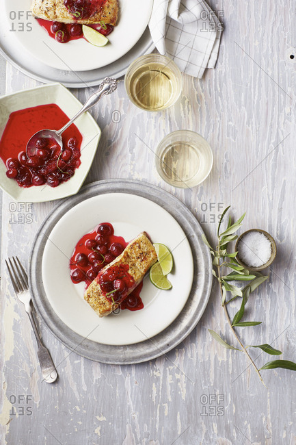 Fish filet with whole cranberry sauce and a glass of white wine