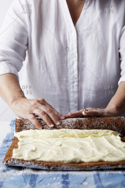 Chef rolling a chocolate pastry filled with icing for roulade