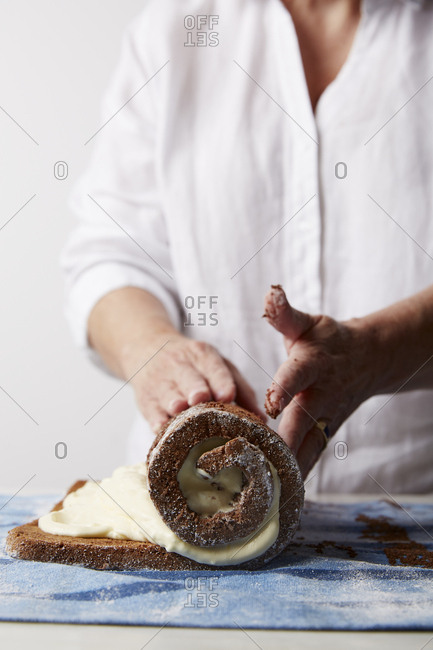Chef rolling a cream-filled pastry to make roulade