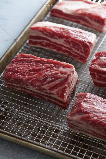 Raw beef lined on a wire rack in a roasting pan