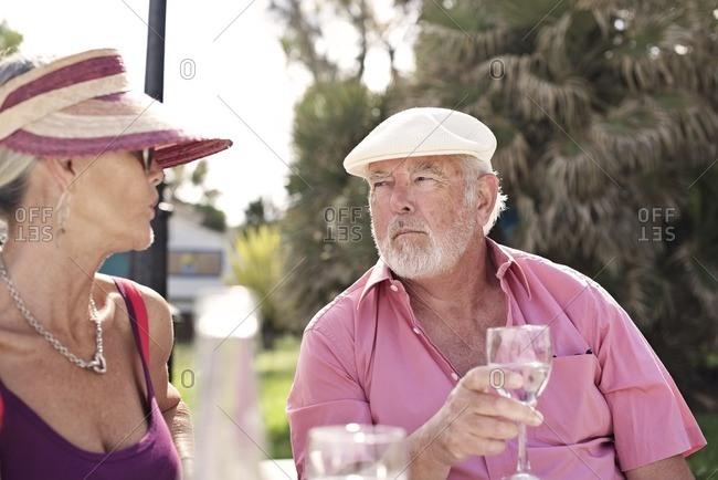 Senior couple having conversation over wine