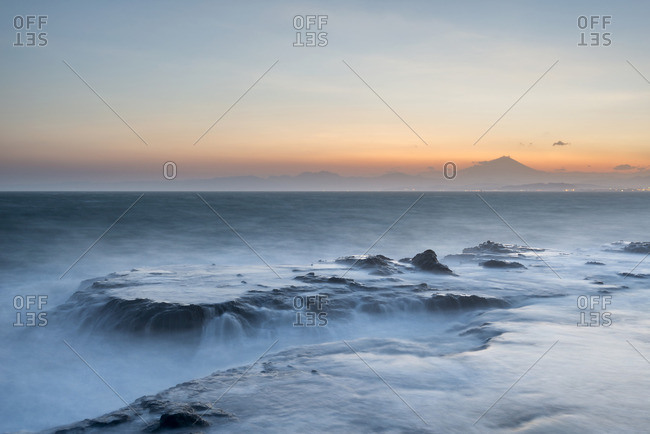 Waves crashing into sea rocks at sunset and Mount Fuji in the background, Enoshima, Kanagawa Prefecture, Japan