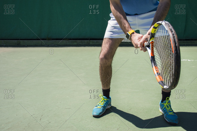 Legs of tennis player with racket