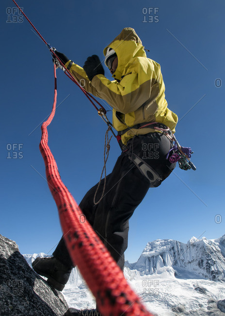 Everest region Ama Dablam, mountaineer with rope at rock face