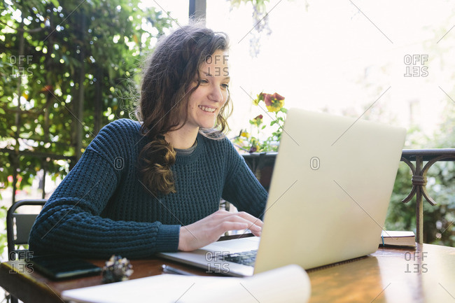 Young woman sitting on balcony using laptop
