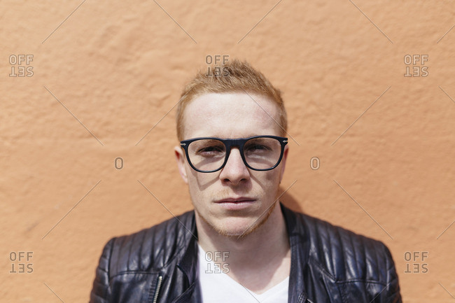 Portrait of strawberry blonde young man wearing black glasses