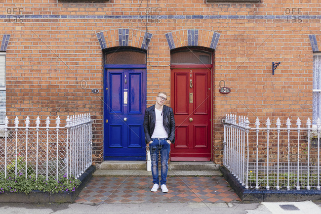 Young man standing in front of a brick house
