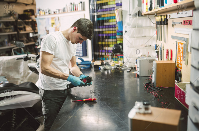 Electronic technician fixing an electronic device at workbench