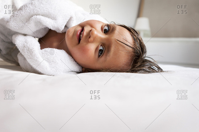 Portrait of little boy with shower towel lying on the bed after taking a bath