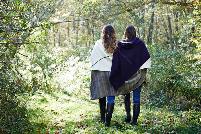Two women walking with blanket around shoulders