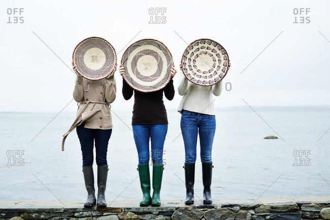 Three women holding round wicker baskets in front of their faces