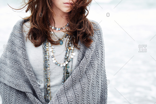 Close up of brunette woman wearing several necklaces