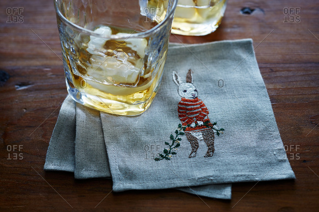 Alcoholic beverage glass on a linen napkin with stitched rabbit