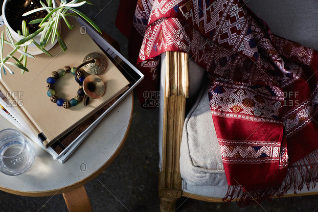 Overhead view of a hand woven blanket on a couch by side table
