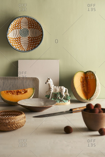 Still life with cantaloupe, figurine, and baskets