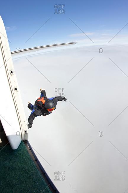 Mid adult man mid air preparing to fly in wingsuit