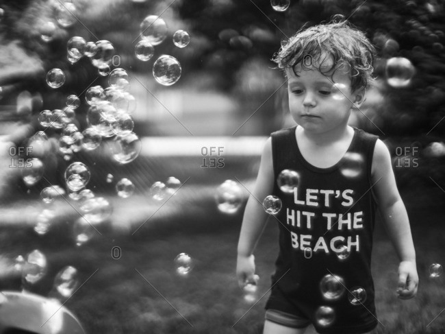 Boy standing among bubbles