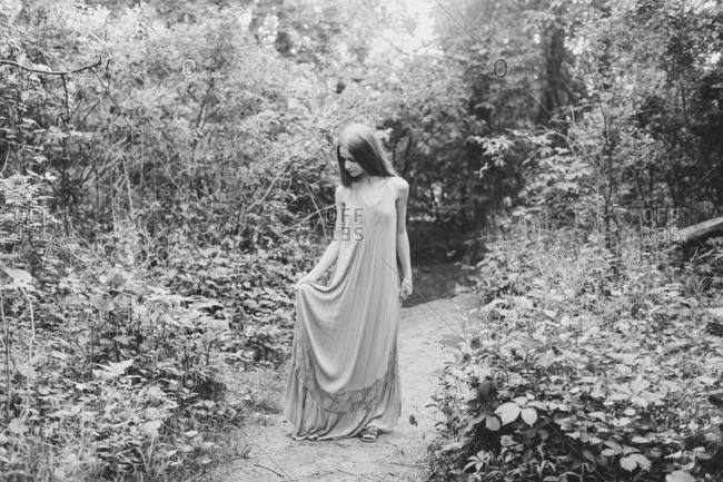 Young woman walking down nature path in black and white