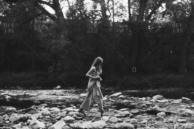 Young woman walking on riverside rocks in black and white