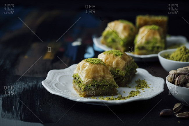 Pistachio baklava slices served on two plates along with a bowl of whole pistachio and  a bowl of ground pistachio.