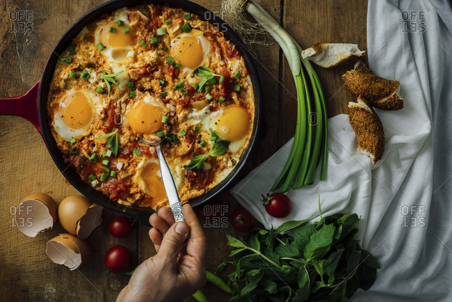 Getting an egg with a spoon from an egg dish called shakshuka or menemen.