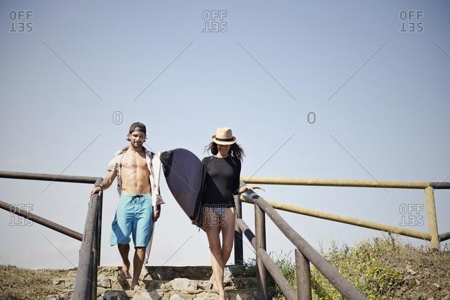 Surfer couple on coastal stairs