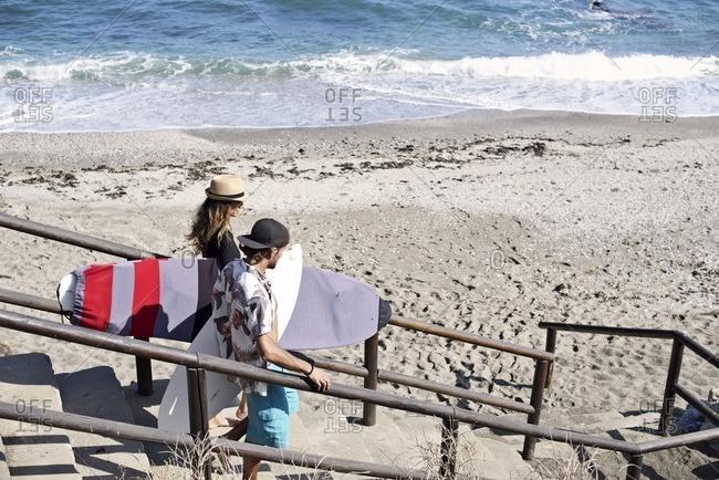 Surfer couple on coastal steps