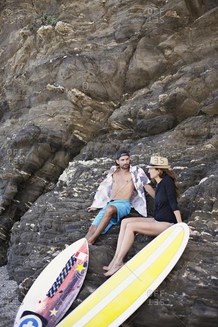 Surfer couple resting on rocks