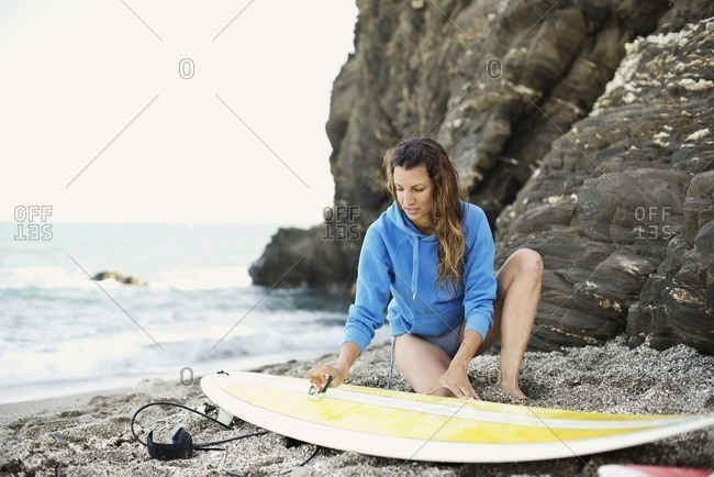 Female surfer checking her board