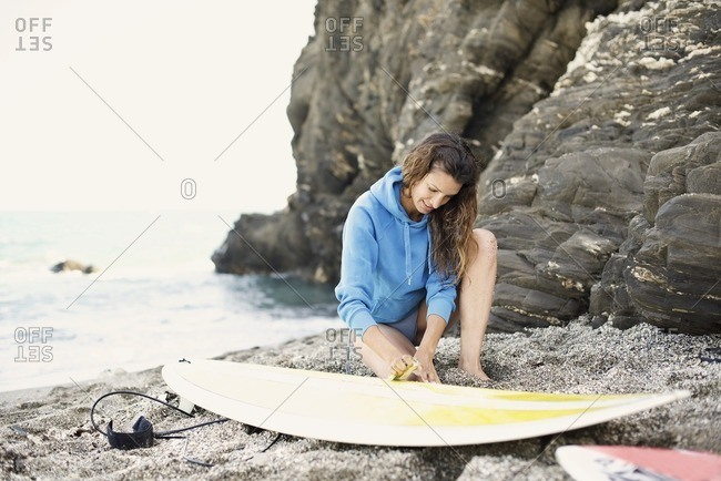 Surfer looking at her board