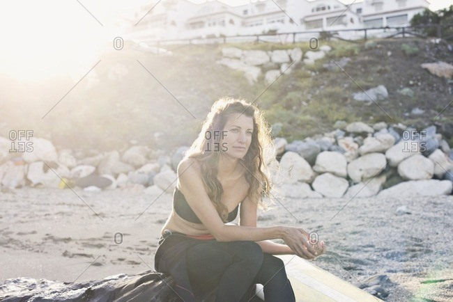 Female surfer sitting contemplatively