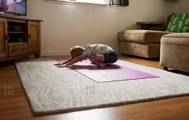 Boy stretching on yoga mat